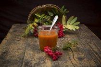 Корзинка, рованье и стакан рованьского варенья на темном дереве — стоковое фото