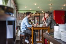 To young men socializing in a cafe — Stock Photo