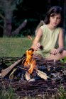 Girl sitting on a meadow behind a camp fire — Stock Photo