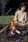 Дівчинка сидить на луг позаду табір вогню — стокове фото