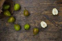 Целом и нарезанные груши с кухонным ножом на темное дерево — стоковое фото