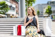 Retrato de una joven sonriente sentada en un banco con bolsas de compras sosteniendo un smartphone - foto de stock