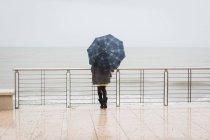 Rückansicht des Frau mit Regenschirm mit Blick auf das Meer — Stockfoto