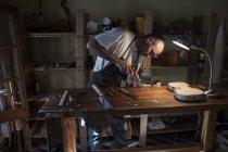 Geigenbauer mit Meißel auf einer Geigenrolle bei der Herstellung einer Geige in seiner Werkstatt — Stockfoto