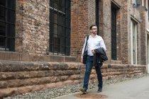 Прогулочный бизнесмен смотрит в сторону мимо кирпичного здания — стоковое фото