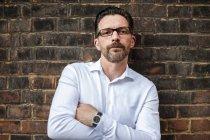 Portrait d'homme d'affaires réservé en regardant la caméra appuyé au mur de briques de verres — Photo de stock