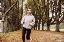 Frau joggt im Herbst im Park — Stockfoto