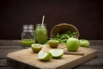 Two glasses of apple kiwi spinach smoothie and ingredients — Stock Photo