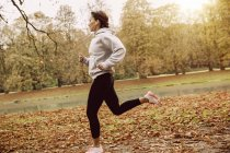 Woman jogging in park during autumn — Stock Photo