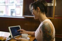 Tattooed young woman sitting in a coffee shop using digital tablet — Stock Photo