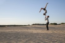 Acrobat couple performing hand to hand stand — Stock Photo