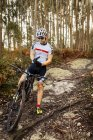 Mountain biker having a rest in the forest — Stock Photo