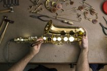 Ansicht von oben abgeschnitten Bild der Instrumentenbauer Demontage Saxophon während der Reparatur — Stockfoto