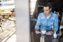 Young man in cafe checking cell phone — Stock Photo