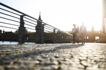 Couple walking by river, pushing bicycle — Stock Photo