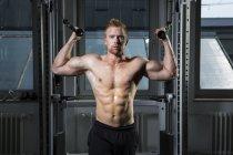 Atleta físico haciendo ejercicio con máquina de cable en el gimnasio - foto de stock