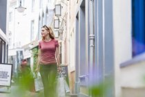 Smiling woman walking on the street carrying shopping bags — Stock Photo