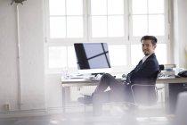 Empresário sentado no escritório, trabalhando no computador — Fotografia de Stock