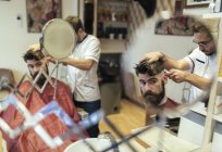 Reflection of barber cutting hair of a customer in barbershop — Stock Photo