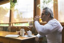 Uomo che si siede al tavolo della colazione bere bicchiere di succo — Foto stock
