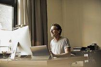 Homme assis au bureau de travail avec ordinateur — Photo de stock