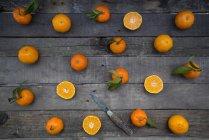 Mandarini e coltelli interi e tagliati a fette su superficie di legno — Foto stock