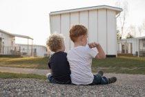 Девочка и мальчик сидят на гравийной дорожке, вид сзади — стоковое фото