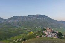 Италия, Умбрия, национального парка Монти Сибиллини, небольшой городок Кастеллуччо ди Норча и гору Vettore на закате — стоковое фото
