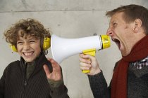 Father and son screaming at each other with magaphone — Stock Photo
