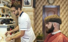 Barber and hipster customer in a barbershop — Stock Photo
