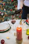 Man serving wine at Christmas dinner — Stock Photo