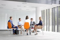 Businesspeople sitting in circle talking — Stock Photo