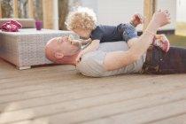 Père, jouer avec la petite fille sur la terrasse — Photo de stock
