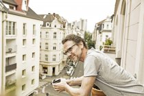Smiling man on balcony looking down the street holding coffee cup — Stock Photo