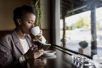 Giovane donna seduta in un caffè utilizzando smartphone mentre beve il caffè — Foto stock