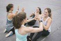 Quattro donne che fanno sit-up durante l'allenamento del boot camp all'aperto — Foto stock
