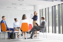 Young Businesswoman talking to colleagues sitting in circle — Stock Photo