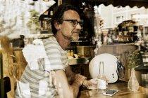 Человек, сидящий за окном кофейни с напитком в стеклянной бутылке — стоковое фото