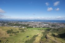 United Kingdom, Scotland, Edinburgh, View over cliffs of Salisbury Crags and old town, Firth of Forth, aerial view — Stock Photo