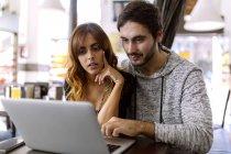 Junges Paar benutzt Laptop in Kneipe — Stockfoto