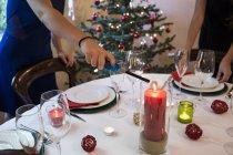 Femme allume une bougie sur la table de dîner de Noël — Photo de stock