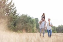 Family of three in field with father carrying daughter on shoulders — Stock Photo