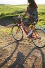 Молодая женщина в платье с цветочным дизайном езда на велосипеде по грунтовой дорожке — стоковое фото