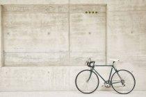 Bicicletta parcheggiata al muro di cemento — Foto stock