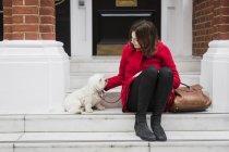 Jovem mulher sentada na escada, além de seu cão — Fotografia de Stock