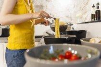 Mujer en la cocina preparando espaguetis - foto de stock