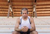 Junger Sportler mit Kopfhörer und Smartphone — Stockfoto