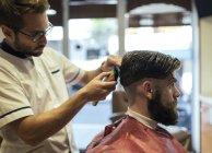 Парикмахерская бреет голову клиента в парикмахерской — стоковое фото
