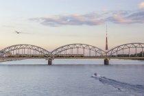 Latvia, Riga, railway bridge and TV Tower at the Daugava River in the evening — Stock Photo