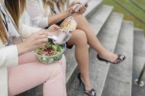Vista recortada de dos mujeres almorzando en la escalera - foto de stock